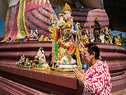 20 SEPTEMBER 2015 - SARIKA, NAKHON NAYOK, THAILAND: A woman prays while she walks around statues of Ganesha at the Ganesh festival at Shri Utthayan Ganesha Temple in Sarika, Nakhon Nayok. Ganesh Chaturthi, also known as Vinayaka Chaturthi, is a Hindu festival dedicated to Lord Ganesh. Ganesh is the patron of arts and sciences, the deity of intellect and wisdom -- identified by his elephant head. The holiday is celebrated for 10 days. Wat Utthaya Ganesh in Nakhon Nayok province, is a Buddhist temple that venerates Ganesh, who is popular with Thai Buddhists. The temple draws both Buddhists and Hindus and celebrates the Ganesh holiday a week ahead of most other places.    PHOTO BY JACK KURTZ