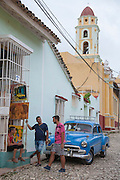 A classic car and three young men talking outside a shop in Trinidad, Cuba