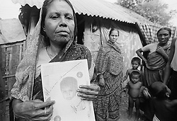 BANGLADESH TONGI ERSHAD COLONY 13OCT00 - Mrs Noorjahan, mother of another child, Yasmin, which had been adopted by Dutch parents, holds up our campaign leaflet asking for the whereabouts of Lisa's biological parents. To date, Mrs Noorjahan and Yasmin (living in the Netherlands) have not met...jre/Photo by Jiri Rezac..© Jiri Rezac 2000..Tel/Fax: +44 (0) 20 8968 9635.Mobile: +44 (0) 7801 337 683..Email: jiri@jirirezac.com.Web: www.jirirezac.com..All pictures © Jiri Rezac 2000. All rights reserved.