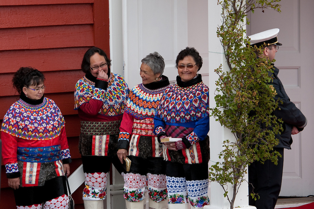 Inuit women sharing a giggle outside Cathedral Annaassisitta Oqaluffia,  Nuuk on Greenland's National Day, wearing traditional Inuit clothing.