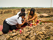02 APRIL 2016 - NA SAK, LAMPANG, THAILAND:  A family of Thai Buddhists pray in the ruined temple of Sobjant village. The village of Sobjant in Na Sak district in Lampang province was submerged when the Mae Chang Reservoir was created in the 1980s. The village was relocated to higher ground a few kilometers from its original site. The drought gripping Thailand drained the reservoir and the foundations of the Buddhist temple in the original village became visible early in 2016. Thai families come down to the original village to pray in the ruins of the temple and look at what's left of the village. This is the first time in more than 30 years that this area has not been under two meters of water.     PHOTO BY JACK KURTZ