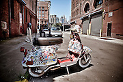 A Vespa with hundreds of stickers is parked on a street of DUMBO, Brooklyn, with the Brooklyn Bridge in the background, 2009.