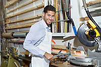 Portrait of a happy young craftsman standing by circular saw machinery
