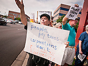 18 APRIL 2011 - PHOENIX, AZ: MICHAEL P., a retired teacher, chants during a picket of US Sen John McCain's office Monday. About 50 members of MoveOn.org gathered at the office of US Sen. John McCain (R-AZ) in Phoenix, AZ, Monday, Apr. 18, to draw attention to corporations that don't pay U.S. taxes. A representative of the group went into McCain's office present the Senator's staff with a tax bill for the 12 corporations they say paid no US income taxes.      Photo by Jack Kurtz