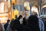 Muslim woman at Hagia Sophia, Ayasofya Muzesi mosque museum wearing niqab using smartphone to take photographs, Istanbul, Turkey