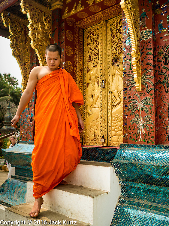 12 MARCH 2016 - LUANG PRABANG, LAOS: A Buddhist monk leaves small prayer chamber at Wat Xieng Thong, Luang Prabang's oldest Buddhist temple,  in Luang Prabang, Laos. Laos is one of the poorest countries in Southeast Asia. Tourism and hydroelectric dams along the rivers that run through the country are driving the legal economy.       PHOTO BY JACK KURTZ