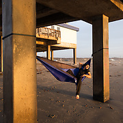 A young man in a hammock is enjoying a sunrise at Horace Caldwell Pier, Port Aransas, Texas.