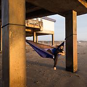 A young man in a hammock is enjoying a sunrise at Horace Caldwell Pier, Port Aransas, Texas.