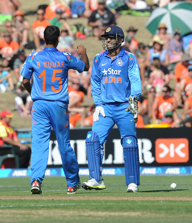 India's MS Dhoni, right, celebrates with Mohammed Shami after he took the catch off his bowling to dismiss New Zealand's Brendon McCullum for 30 in the first one day International cricket match, McLean Park, New Zealand, Sunday, January 19, 2014. Credit:SNPA / Ross Setford