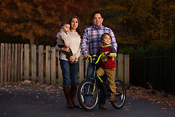 The Hinojosa family posed for a portrait at their home, Thursday, Nov. 07, 2013 at  in . <br /> <br /> The family just moved to Louisville two weeks ago from Texas for a job. <br /> <br /> Pictured are Ozil, 1, left, Erika, Omar, and Octane, 5.