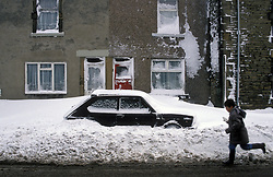 Snow covered car in residential street; Co Durham UK