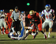 Lafayette High's D.K. Buford (2) runs through attempted tackle by Memphis University School's MaLeik Gatewood (13) in Oxford, Miss.  on Friday, September 27, 2013. MUS won.