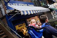 """8 Novembre, 2008. Brooklyn, New York.<br /> <br /> Padre e figlia aspettano davanti all'entrata del Blue Apron Foods nella Union Street a Park Slope, Brooklyn, NY, una delle vie più famose del quartiere. Park Slope, spesso definito dai newyorkesi come """"The Slope"""", è un quartiere nella zona ovest di Brooklyn, New York, e confinante con Prospect Park.  Park Slope è un quartiere benestante che ha il maggior numero di nascite, la qualità della vita più alta e principalmente abitato da una classe media di razza bianca. Per questi motivi molte giovani coppie e famiglie decidono di trasferirsi dalle altre municipalità di New York a Park Slope. Dal punto di vista architettonico, il quartiere è caratterizzato dai brownstones, un tipo di costruzione molto frequente a New York, e da Prospect Park.<br /> <br /> ©2008 Gianni Cipriano for The New York Times<br /> cell. +1 646 465 2168 (USA)<br /> cell. +1 328 567 7923 (Italy)<br /> gianni@giannicipriano.com<br /> www.giannicipriano.com"""