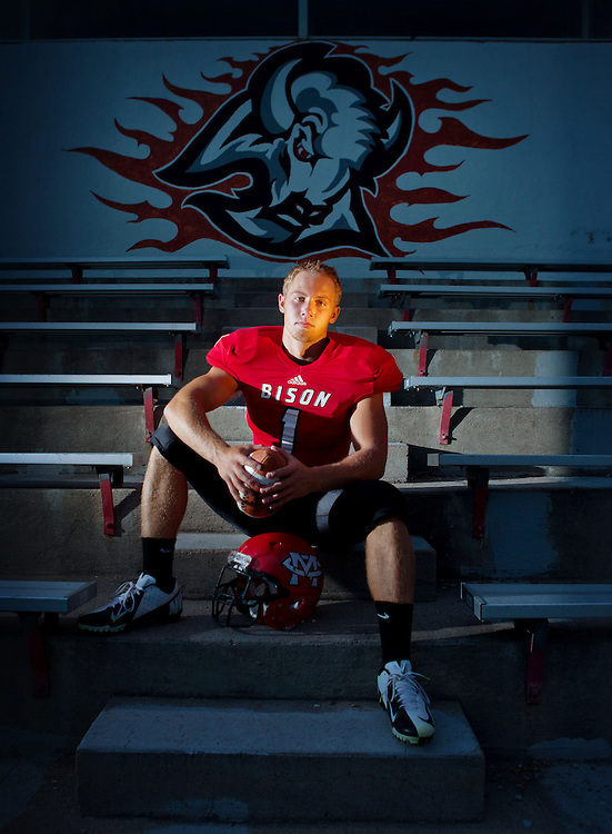 McCook running back and offensive linebacker poses for a portrait below a McCook Bison emblem at Weiland Field in McCook on Wednesday, July 25, 2012. | Chicago Freelance Photographer | Alyssa Schukar | Photojournalist