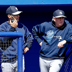 Mar 14, 2013; Dunedin, FL, USA; New York Yankees manager Joe Girardi (28) calls to the bullpen as pitching coach Larry Rothschild (58)  looks on from the dugout during the bottom of the fourth inning of a spring training game against the Toronto Blue Jays at Florida Auto Exchange Park. Mandatory Credit: Derick E. Hingle-USA TODAY Sports