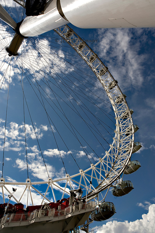 Looking upward a half the circumference of the London Eye with its supporting pillar along the top of the vertical image.  Its circular shape with dangling passenger pods and fine wire spokes make a strong pattern against the bright blue sky sprinkled with bright white clouds.