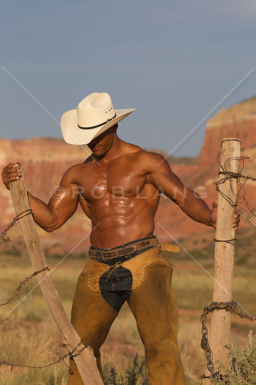 sexy and rugged African American Cowboy without a shirt working on a fence outdoors