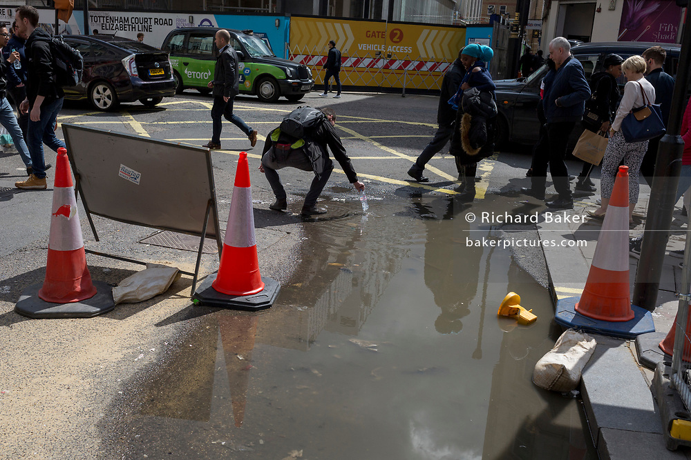 A person picks-up a water bottle after dropping it in a puddle on Oxford Street after heavy rain the previous day, on 1st May, in London, England.