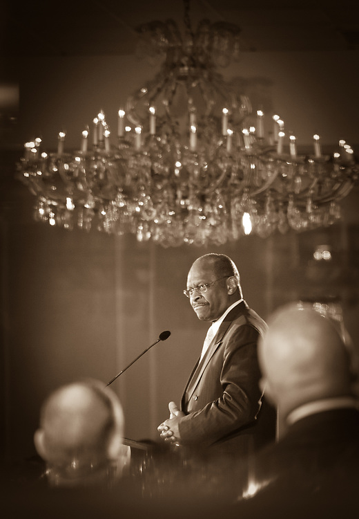 Presidential hopeful Herman Cain is reflected in a ballroom mirror as he speaks during a campaign Rally in the Radisson Hotel in Nashua, NH.
