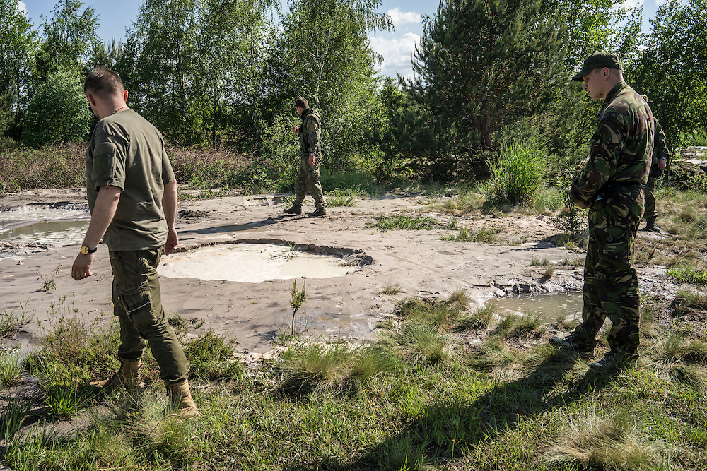 Members of a special police unit from Kyiv search an illegal amber mining site for contraband amber and mining equipment on Monday, May 30, 2016 in Netreba, Ukraine.