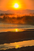 Rising fog on the Deasadeash River at sunrise and the Kluane Ranges, the easternmost of the St Elias Mountains. <br />
