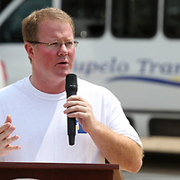 Tupelo Mayor Jason Shelton stands near one of the Transit Buses as he speaks to those in attandance at the Countdown to Tupelo Transit unveiling Wednesday afternoon at Fairpark in Tupelo.