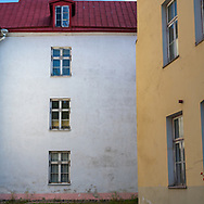Photo of a white and yellow walls of  two buildings at roght angles to each other.