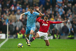 MANCHESTER, ENGLAND - Sunday, January 8, 2012: Manchester City's Aleksandar Kolarov in action against Manchester United's Antonio Valencia during the FA Cup 3rd Round match at the City of Manchester Stadium. (Pic by David Rawcliffe/Propaganda)