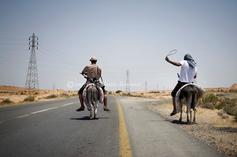 LIBYAN ARAB JAMAHIRIYA, Bir al Ghanam : Libyan rebel ride donkeis to reach the front in the outskirts of the Libyan village held by the Qaddafi loyalists, Bir al Ghanam on July 12, 2011. ALESSIO ROMENZI