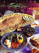 Alaska. Cooking baked wild salmon with fresh vegetable platter.