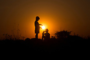 A young boy is offering the setting sun to the young girl next to him