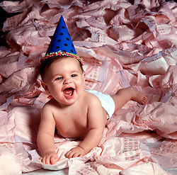 young baby with party hat laying on large assortment of disposable diapers non green eco friendly pollution landfill