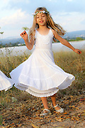 Young girl of six, in white dress and a wreath of flowers on her head in a field celebrating Shavuot the spring harvest festival
