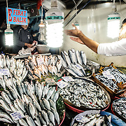 A salesman catches a package of fish at the Karakoy Fish Market in Istanbul near the Galata Bridge.