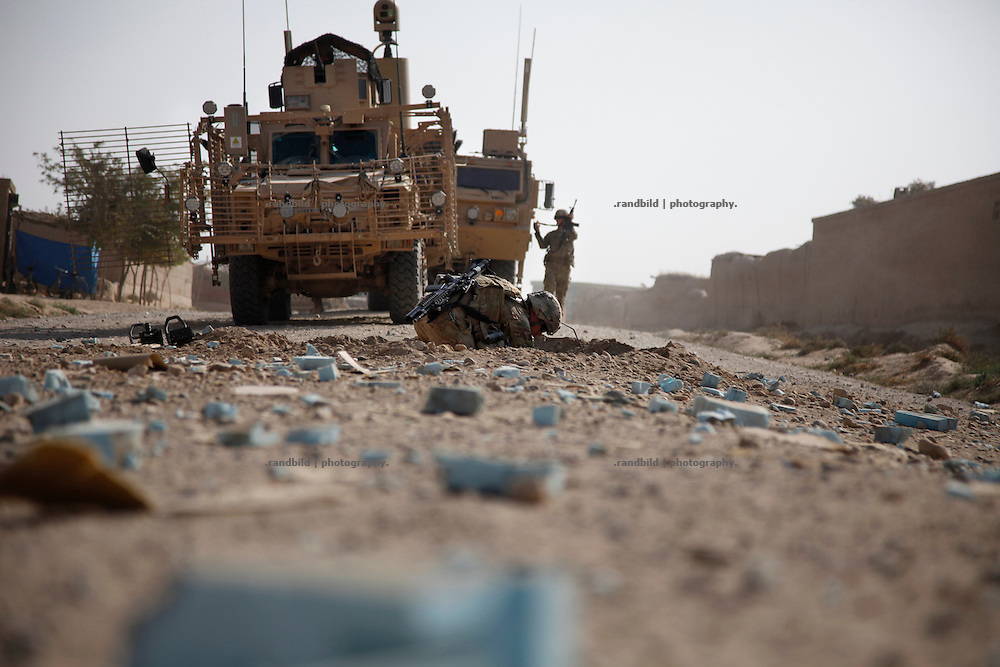 Members of the RCP platoon collect debris and conservate evidences in and around the bomb crater shortly after their unit was hit by an IED in Nawabad. A Route Clearance Package patrols to identify hidden IED´s along a certain road.
