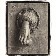 An old  knocker in the form of a hand graces a weathered door with peeling paint in Orvieto, Italy.