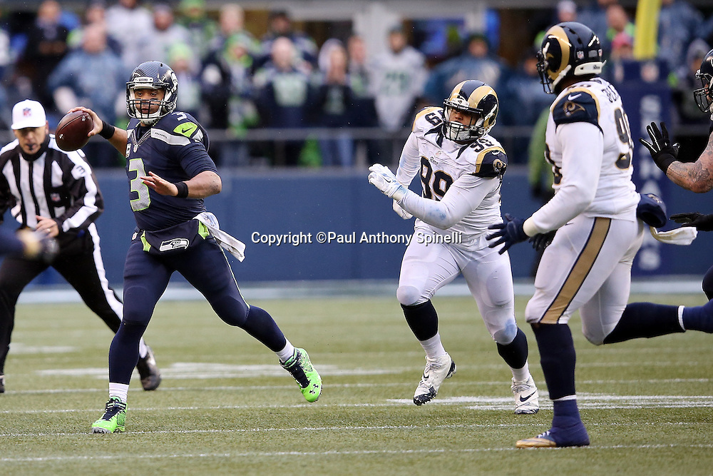 Seattle Seahawks quarterback Russell Wilson (3) looks to pass while being chased by St. Louis Rams defensive tackle Aaron Donald (99) during the 2015 NFL week 16 regular season football game against the St. Louis Rams on Sunday, Dec. 27, 2015 in Seattle. The Rams won the game 23-17. (©Paul Anthony Spinelli)