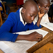 Kenya. Siaya. Agoro Oyombe Primary . Abraham Otieno, 13, lost his leg when he was involved in a road accident.  In class.
