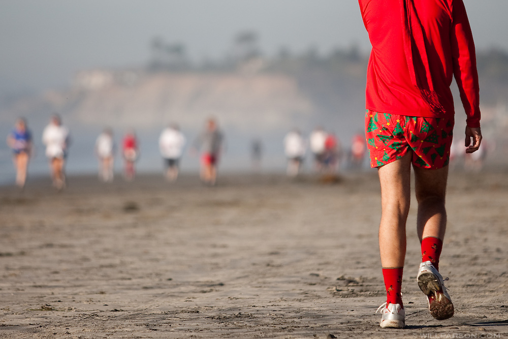 A participant in holiday-themed shorts watches the other runners complete the Red Nose Run.