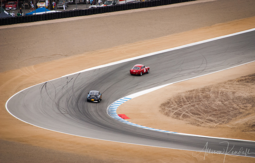 Two cars race through the turns of Laguna Seca during the Rolex Monterey Motorsports Reunion races at Laguna Seca, during Monterey Car Week