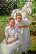 twins Carmel and Carol McNamee in their communion dresses, with family pony Silver