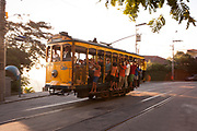 PEOPLE HANGING OFF A YELLOW TRAM WITH BRIGHT SUNSHINE RIO
