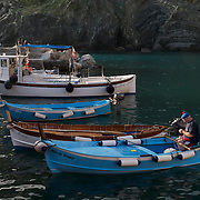 A local fisherman working overtime on his boat in the seaside village of Riomaggiore, Italy