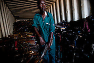 A man salvages gun parts from a container of guns siezed during governmental disarmnament campaigns.