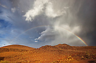 Rainbow with stormy sky over mountains in the Sahara desert of Morocco.