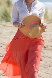 Woman Walking on Beach Holding Straw Hat, Cropped view