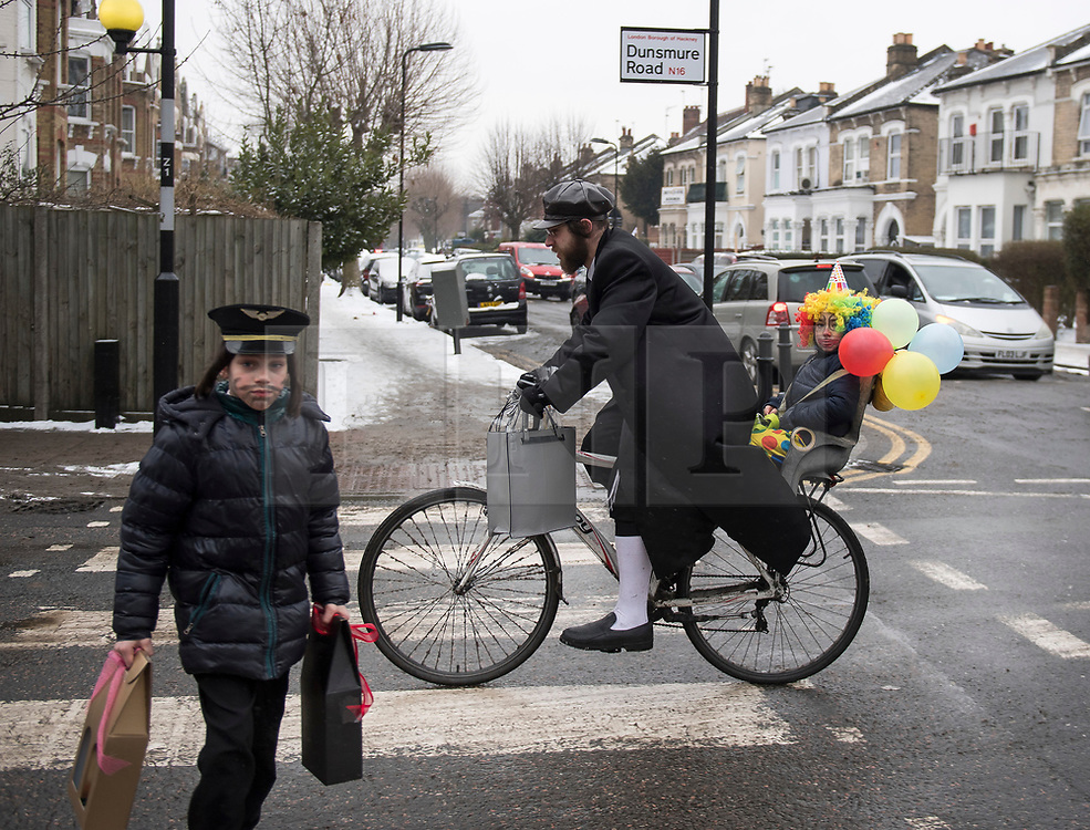 © Licensed to London News Pictures. 01/03/2018. London, UK. An Orthodox Jewish man rides his bike, carrying his child through the streets of  Stamford Hill in north London, during celebrations for the festival of Purim on March 1, 2018. Purim celebrates the miraculous salvation of the Jews from a genocidal plot in ancient Persia, an event documented in the Book of Esther. Traditionally the jewish community wear fancy dress and exchange reciprocal gifts of food and drink. Photo credit: Ben Cawthra/LNP
