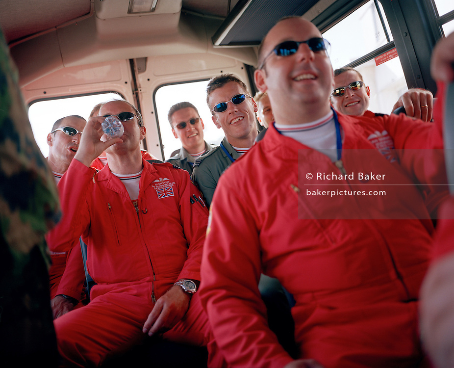 Pilots of the 'Red Arrows', Britain's Royal Air Force aerobatic team ride in crew bus after air show display.