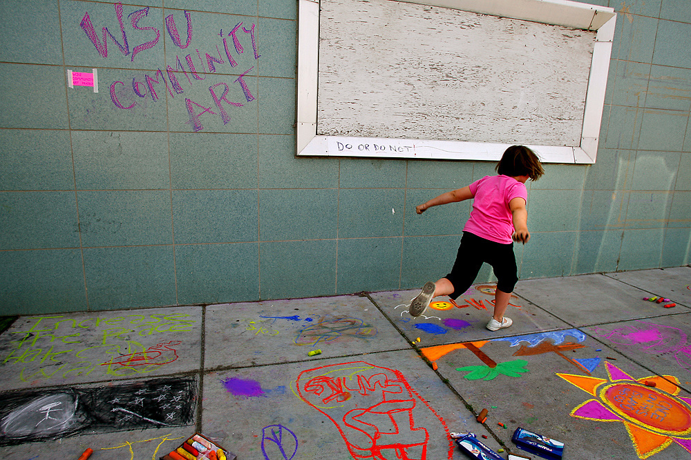 "A young girl skips through Washington State University Tri-Cities' community art section during Richland's annual Chalk Art Festival. Student Daniel Anderson described it as ""Dialogical Art"" -- art that is created through the interactions and dialogue created by bringing people together. They encouraged any passersby to add to the piece and discouraged people from walking around it, saying that footsteps and smearing was as much a part of the process."