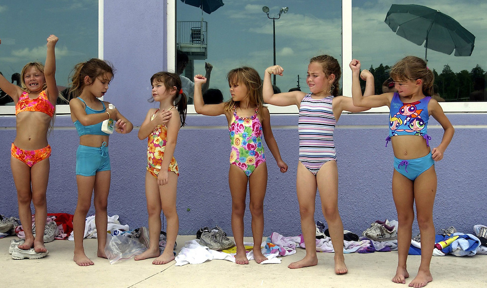 Some summer campers give their best girl power flex as others finish applying their sunscreen while, from left, Cearra Moawad (cq), Brianna Leone (cq), Brianna Wright (cq), Lia Kass (cq), Maria Mansolillo (cq) and Alexandra Marshall (cq) wait to take their swim test and enter the pool during the first week of summer camp Wednesday at the James P. Gills Family YMCA in Trinity..(ALL CQ'S FROM CAMP ADMINISTRATORS)